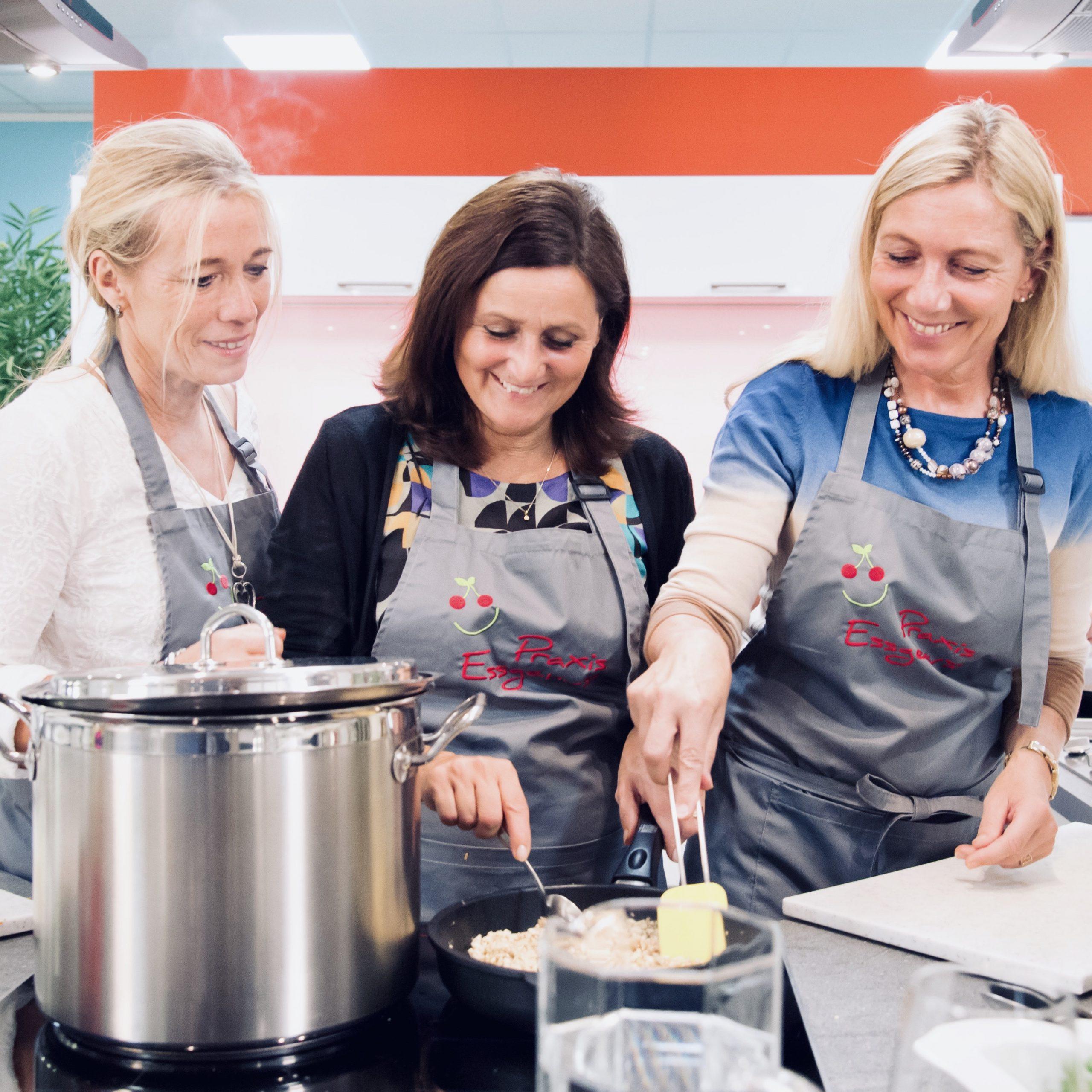 Drei Frauen inklusive Ernährungsberaterin Andrea Stallmann stehen an einem Herd mit Kochtöpfen und lachen.